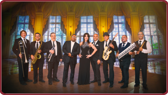 Posed photo of Debbie Taylor Band in a ballroom holding instruments